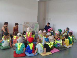 Jemand liest einer Gruppe von Kindern etwas vor.