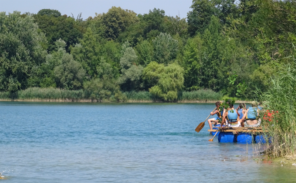 Menschen sitzen auf einem Floß und paddeln über einen blauen See.