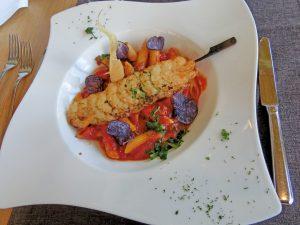 Ein Teller mit einem Shrimps-Spieß und Spaghetti Bolognese.