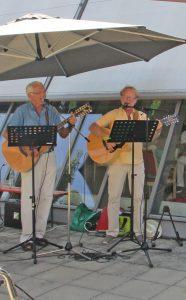 Zwei Männer stehen an Gitarren und singen.