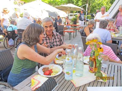 Ein Mann und eine Frau sitzen an einem Tisch und essen Grillwurst.
