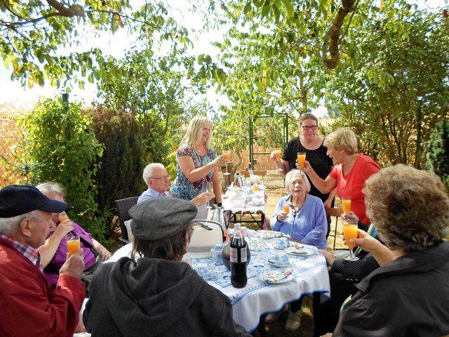 Menschen sitzen in einem Garten an einem Tisch und prosten sich zu.