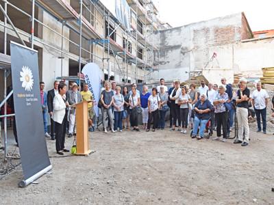 Eine Frau steht an einem Rednerpult auf einer Baustelle, viele Menschen stehen in einem Halbkreis daneben.