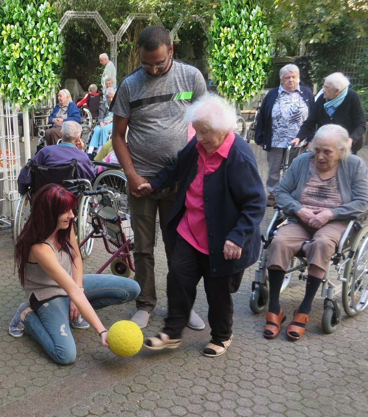 Eine Frau kniet auf dem Boden und hält einen Ball fest, den einen