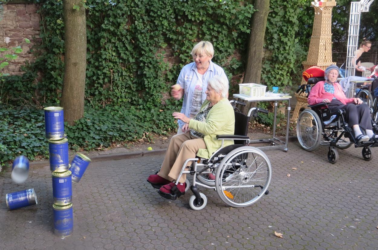 Eine Seniorin sitzt im Rollstuhl und wirft einen Ball auf eine Dosenpyramide.