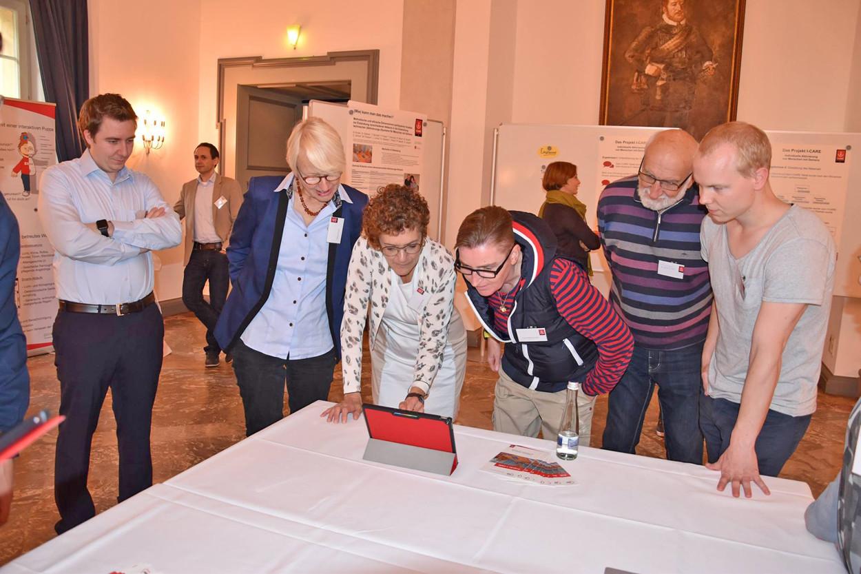 Menschen stehen an einem Tisch und schauen auf einen Tablet-PC