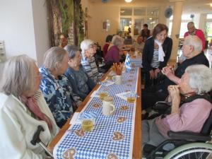 Menschen sitzen an einem langen Tisch und trinken Bier.