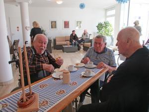 Männer sitzen zusammen an einem Tisch und trinken Bier.