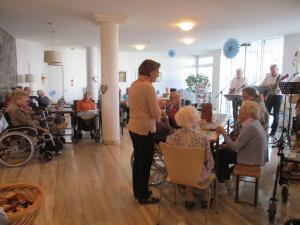 Blick in den Raum eines Seniorenzentrums mit Menschen während einer Feier.