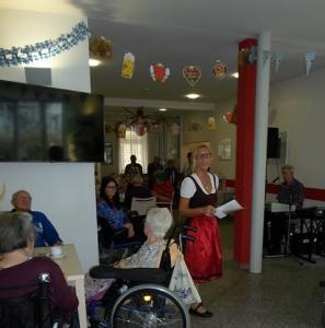 Eine blonde Frau steht in einem roten Dirndl in einem Seniorenzentrum.