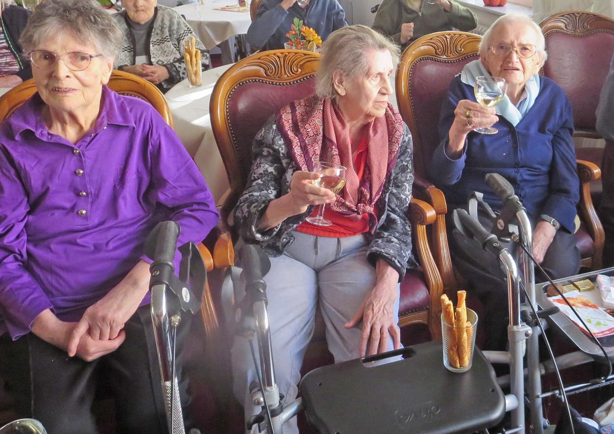 Senior*innen sitzen zusammen in Rollstühlen und trinken Wein.