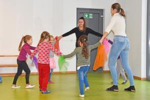 Kinder stehen im Kreis und fassen sich an den Händen.