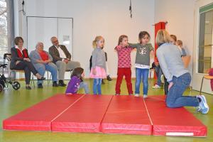 Kinder turnen auf einer Sportmatte.
