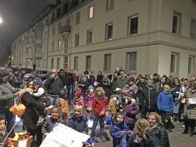 Menschen mit Laternen stehen nachts auf einer Straße.