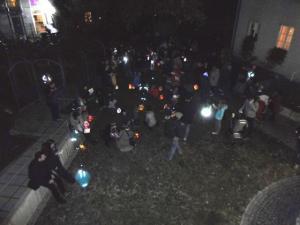Menschen mit Laternen laufen nachts über eine Straße.