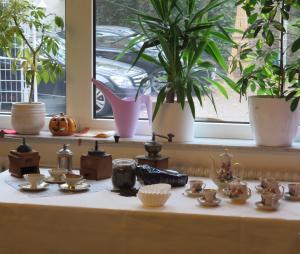 Kaffeekannen und Tassen stehen zusammen mit Kaffeemühlen auf einem gedeckten Tisch.
