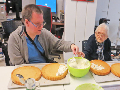 Ein junge Mann und eine ältere Damen backen zusammen Kuchen.