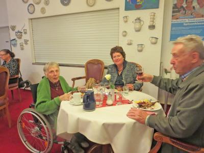 Drei Menschen sitzen an einem Tisch und essen eine Martinsgans.