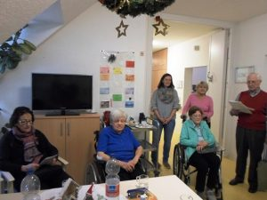 Zwei Frauen sitzen in einem Rollstuhl, daneben stehen zwei weitere Frauen.