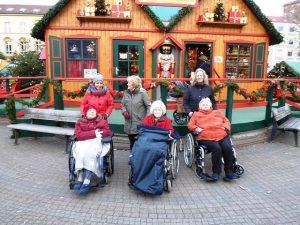 Drei Frauen sitzen im Rollstuh. Hinter ihnen stehen drei Frauen und man sieht dahinter eine Weihnachtsmarkt-Holzhütte.