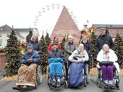 Frauen und Männer sitzen in Rollstühlen vor der Karlsruher Pyramide auf dem Marktplatz, dahinter ist das Glücksrad vor dem Schloss zu sehen.