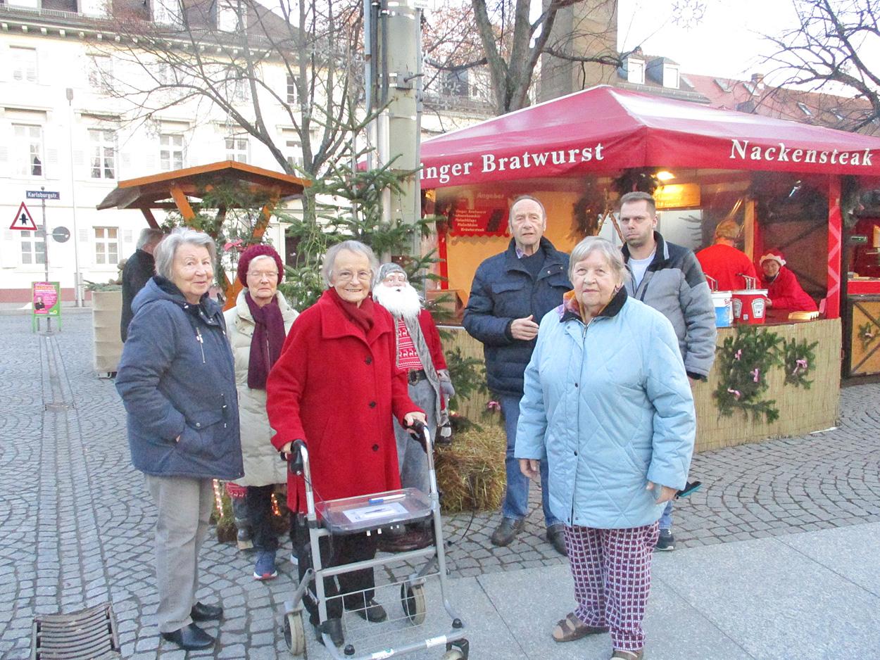 Frauen und Männer stehen vor einer Bude auf dem Weihnachtsmarkt.