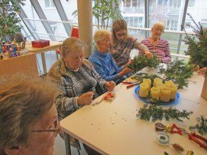 Frauen sitzen an einem Tisch und basteln.