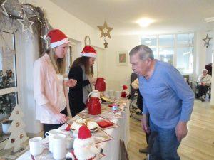 Ein Mann steht vor einem Tisch und holt sich Glühwein von zwei Frauen mit Weihnachtsmann-Mütze.