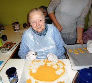 Eine Seniorin sticht Keksteig aus.