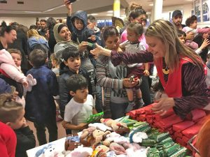 Eine Frau verteilt Geschenke an Kinder.
