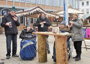 Menschen stehen an einem Tisch im Freien und trinken etwas.