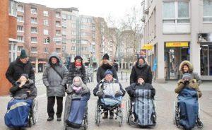 Menschen stehen und sitzen im Rollstuhl in der Stadt und schauen in die Kamera.