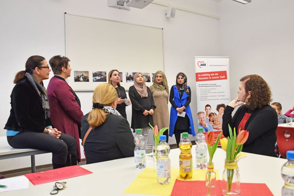 Vier Frauen stehen vor einer Tafel, links daneben steht noch eine Frau und eine Frau Sitzt auf einem Tisch. Eine weitere Dame sitzt vorne an einem Tisch.