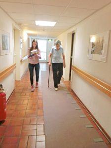 Eine Seniorin und eine Studentin laufen nebeneinander her.