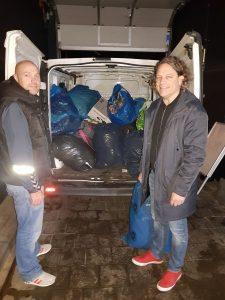 Zwei Männer stehen vor einem Transporter, der mit Müllsäcken gefüllt ist.