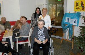 Eine Seniorin sitzt auf einem Stuhl, hinter ihr stehen zwei Frauen und lächeln.
