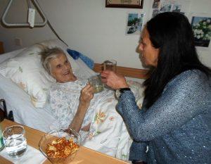 Eine Frau mit dunklen, langen Haaren, sitzt neben einer Seniorin auf dem PFlegebett und prostet ihr zu.