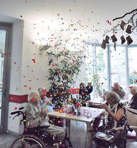 Senioren sitzen an Tischen in einem Konfetti-Regen.