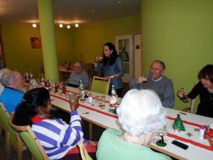 Senioren sitzen an einem Tisch und Prosten sich zu.