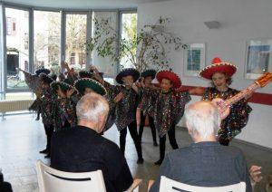 Mädchen und Jungen verkleidet mit Sombreros stehen vor Senioren und machen Musik.