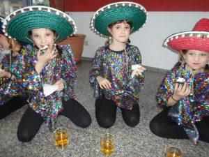 Drei Mädchen sitzen mit Sombreros auf dem Boden und essen etwas.