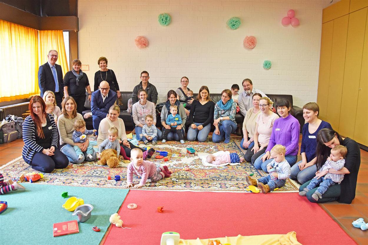 Eine Gruppe von Müttern sitzt auf einem Teppich und spielt mit ihren Babys.
