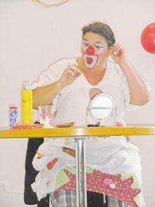 Clownin sitzt am Tisch und schminkt sich.