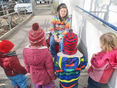 Mädchen sitzt im Rollstuhl und erzählt Kindern etwas