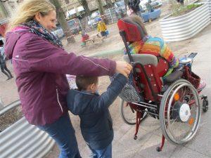 Junge schiebt mit Erzieherin Rollstuhl vom Mädchen