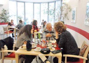 Frauen und Männer sitzen an einem Tisch und schauen in die Kamera
