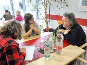 Frauen sitzen an eiFrauen und Männer sitzen an einem Tisch und schauen in die Kameranem Tisch und schauen in die Kamera