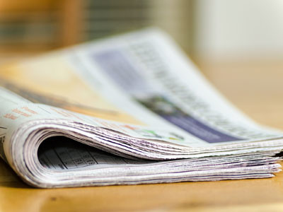Bild von einer Zeitung, die auf einem Tisch liegt.