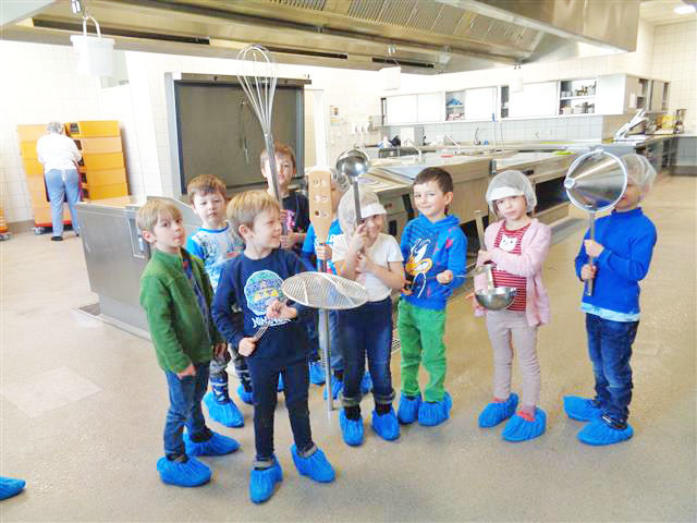 Acht Kinder stehen in der Küche und haben Mützen auf.
