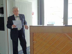 Ein älterer Mann im Anzug steht neben einem Klavier.